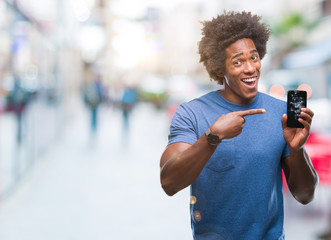 Afro american man holding broken smartphone over isolated background very happy pointing with hand and finger