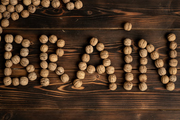 Brain inscription made of walnuts on a wooden background