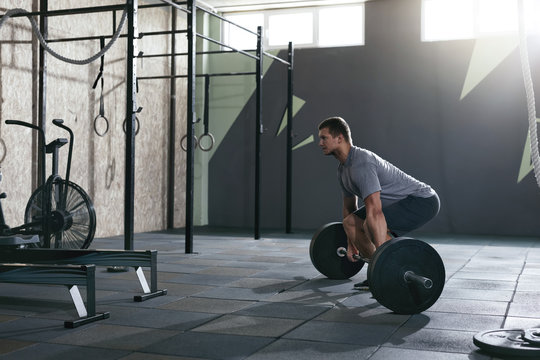 Deadlift. Sports Man Lifting Barbell Row At Gym