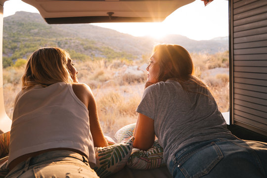 Attractive women lying in a camper van enjoying the Mountain View during sunset. Road trip, best friend.