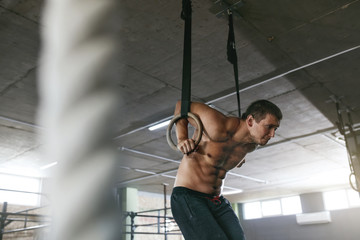 Sports Man Training With Gymnastics Rings At Gym