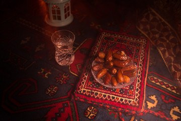 Water and dates. Iftar is the evening meal. View of decoration Ramadan Kareem holiday on carpet. Festive greeting card, invitation for Muslim holy month Ramadan Kareem. Dark background