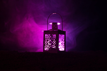 Ornamental Arabic lantern with burning candle glowing at night on dark toned foggy background. Festive greeting card, invitation for Muslim holy month Ramadan Kareem.