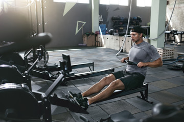 Functional Training. Man Doing Exercise On Rowing Machine At Gym