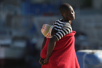 Migrant woman carries a child after disembarking a rescue boat at the port of Malaga