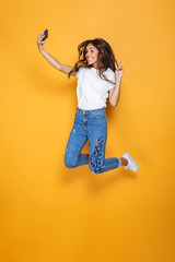 Full length portrait of a happy girl with long dark hair jumping