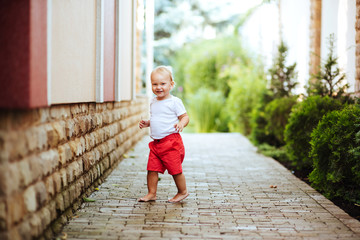 Funny blond toddler boy in summer garden