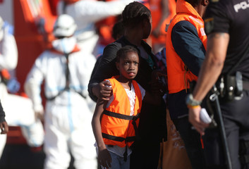 Migrant child looks at a Spanish police officer after disembarking a rescue boat at the port of Malaga