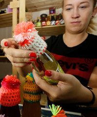 Olesya Ushakova, an emloyee of TastyTaiga online shop producing and selling authentic Siberian wild berries jam and gifts, decorates bottles with miniature wool hats in Krasnoyarsk