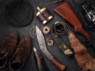 Self adhesive Wall Murals Hunting Flat lay with hunting accessoties over the grey background: old boots, hat, rifle, knives, rope, belt, fox tail.