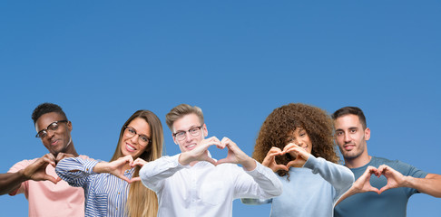 Composition of group of friends over blue blackground smiling in love showing heart symbol and shape with hands. Romantic concept.