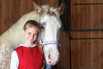 Horsewoman with his horse in the stable