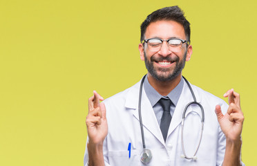 Adult hispanic doctor man over isolated background smiling crossing fingers with hope and eyes closed. Luck and superstitious concept.