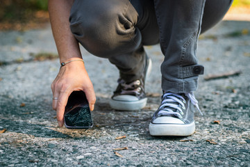Woman lifting up cracked smartphone from the ground