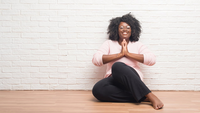 Young african american woman sitting on the floor at home praying with hands together asking for forgiveness smiling confident.