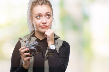 Young blonde woman taking pictures using vintage camera over isolated background serious face thinking about question, very confused idea