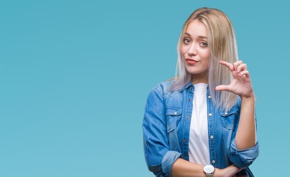 Young blonde woman over isolated background smiling and confident gesturing with hand doing size sign with fingers while looking and the camera. Measure concept.