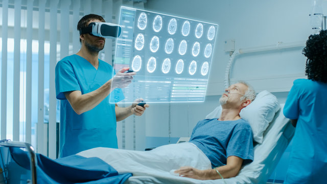 Doctor Wearing Virtual Reality Headset and Holding Joysticks Cures Senior Patient who is Lying in Bed. He Uses Augmented Reality Interface, Looks at Brain Scans and Medical History. Nurse Does Checkup