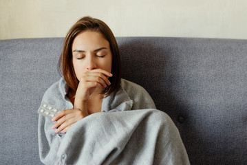 Young attractive woman, feeling sick, taking pills, wrapped in plaid. Sitting on the sofa, at home.