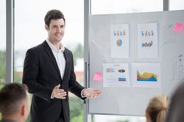 happy business man smiling and making a presentation on whiteboard  and pointing on the chart . boss presenting strategy of marketing to goal of success with teamwork  in meeting room on windows