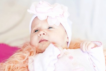 A cute Caucasian newborn baby girl with a flower head band lying on a bed. Curious look. New life concept. One month old baby.