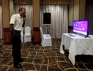 Maldives' former President Mohamed Nasheed watches the Maldivian presidential election results on TV at a hotel in Colombo