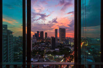 Glass window in room with view at beautiful sunset. Cityscape background image. Fototapete