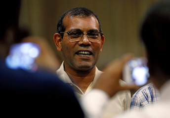 Maldives' former President Mohamed Nasheed smiles as he watches the Maldivian presidential election results on a TV at a hotel in Colombo