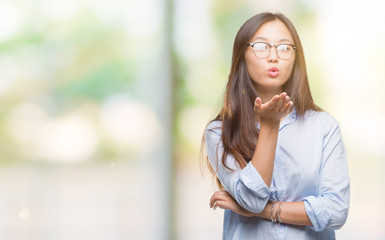 Young asian business woman wearing glasses over isolated background looking at the camera blowing a kiss with hand on air being lovely and sexy. Love expression.