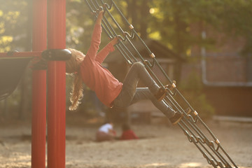 young blonde girl climbing on a climbing net of a playground in a schoolyard in bright sunny light