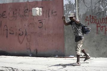 A man throws a cement block during a march to demand an investigation into the alleged misuse of Venezuela-sponsored PetroCaribe funds by previous administrations, in Port-au-Prince