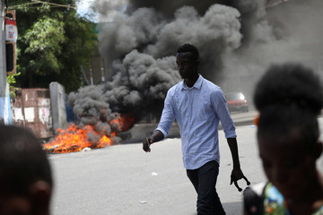 Pedestrians walk next to burning tires after a march to demand an investigation into the alleged misuse of Venezuela-sponsored PetroCaribe funds by previous administrations, in Port-au-Prince