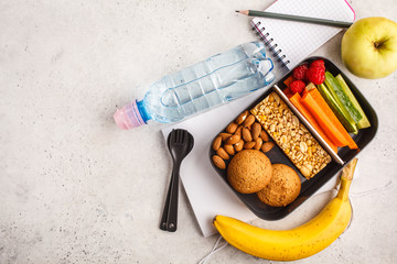 Healthy meal prep containers with cereal bar, fruits, vegetables and snacks. Takeaway food on white background, top view.