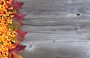 Left border of Halloween trick or treat candies and leaves on rustic wooden boards