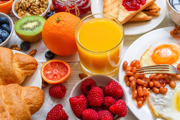 Breakfast including coffee, fried egg ,bacon, beans, croissant, orange juice with nuts, fruits and berries with fork