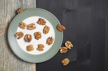 Few walnuts in a plate and near