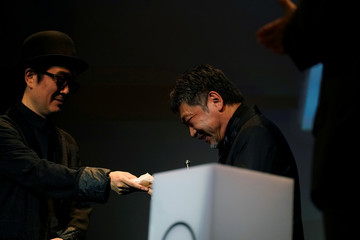 Japanese film director Hirokazu Koreeda is offered a tissue by actor Lily Franky after receiving his Donostia Award for Lifetime Achievement at the San Sebastian Film Festival