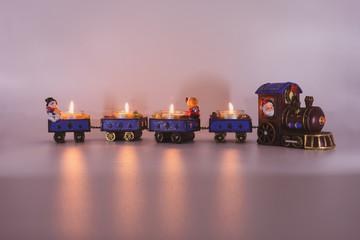 Weihnachtseisenbahn mit brennenden Teelichtern und Lichtschein
