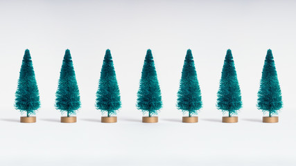 Small artificial Christmas trees on white background. Minimal style. Christmas and New Year concept.