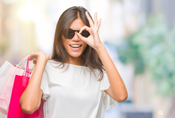 Young asian woman holding shopping bags on sales over isolated background with happy face smiling doing ok sign with hand on eye looking through fingers