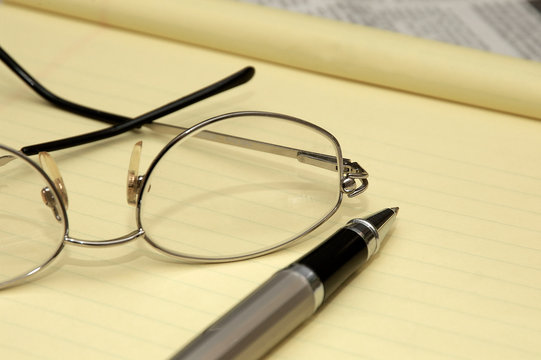 A yellow lined legal pad, reading glasses and a ballpoint pen in an office.
