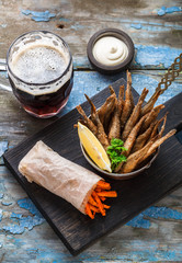 Beer snack deep fried small fishes with carrots sticks