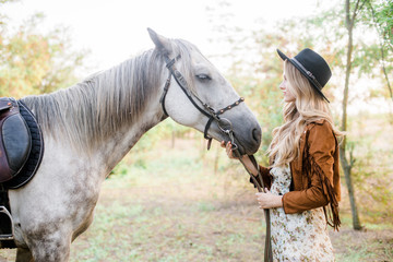 Beautiful  young girl with blond hair in a suede jacket with a fringe , wearing black floppy hat, smiling and stroking her horse in sunset