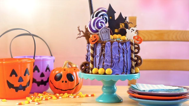 On trend Halloween candyland fantasy novelty drip cake in colorful party setting.
