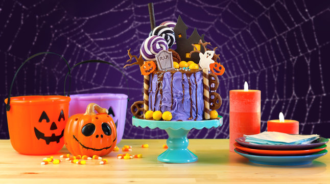 On trend Halloween candyland fantasy novelty drip cake in purple theme colorful purple spiderweb party table setting.