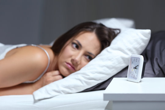 Insomniac woman looking at alarm clock in the night