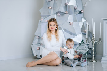 Young caucasian mother with little son  near Christmas tree. Concept of celebrating winter holidays and playing with baby.