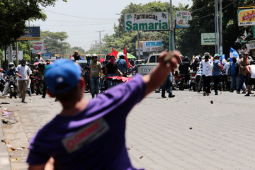 A demonstrator clashes with supporters of Nicaraguan president Daniel Ortega's government in Managua