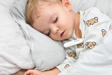 Cute little boy sleeping on a pillow with the thermometer.Measure the temperature