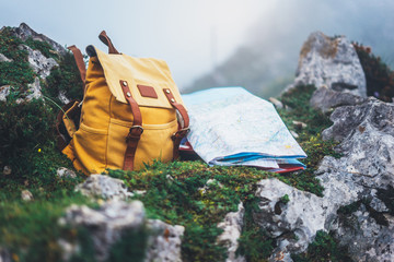 Fototapeta Hipster hiker tourist yellow backpack and map europe on background green grass nature in mountain, blurred panoramic landscape, traveler relax holiday concept, view planning wayroad in trip vacation
